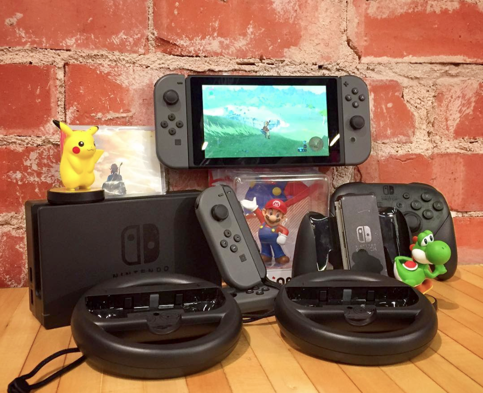 Nintendo Switch console with Pokemon, Yoshi, and Mario Amiibo figures. A Zelda game is shown on the Switch screen.