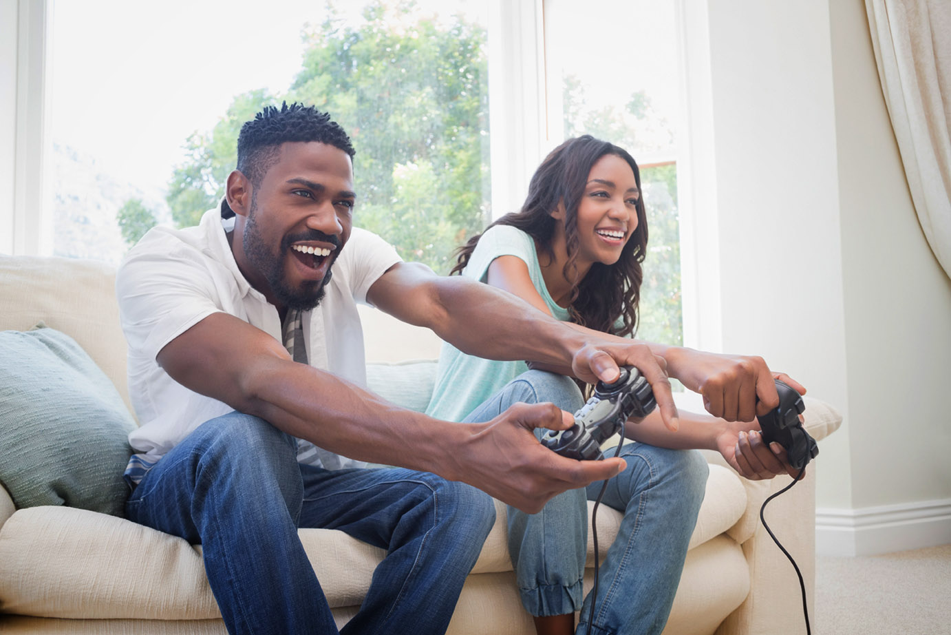 Couple playing video games together on a couch