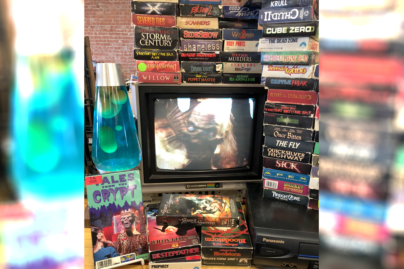 Stack of VHS tapes and a lava lamp surrounding a television set with Tales from the Crypt playing on it