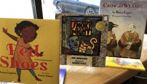 Children's books on a shelf in front of a window including Red Shoes and Crow and Weasel