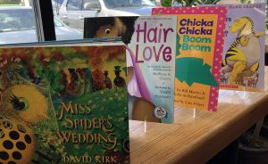 dr. seuss alternative books like Hair Love and Miss Spider's Wedding on a shelf in front of a window