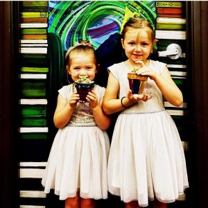 two little girls holding plants standing in front of artist Galadriel's painted selfie spot at Bookmans Northwest