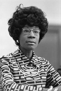 Portrait of Shirley Chrisholm facing forward with a challenging stare, she looks about to speak. She is just one of the Black women who inspires us daily.