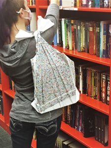 A woman carries a reusable shopping bag over one shoulder, the bag has flower print, and fills it with books from an orange bookshelf. Earth Day is a great day to update your totes.