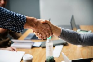 Man and woman shaking hands across a table at the end of a meeting