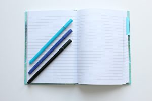 blank binder book with blue pencils