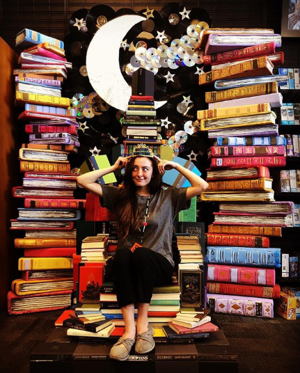 Bookmans employee sitting on a throne made of books and wearing a crown at Bookmans East