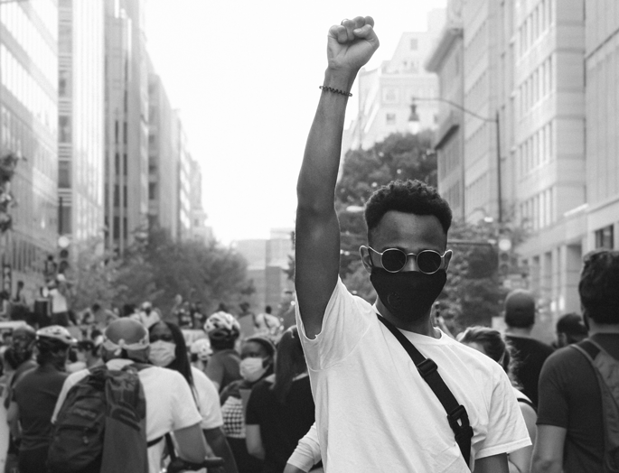 young black man with his arm up at a protest