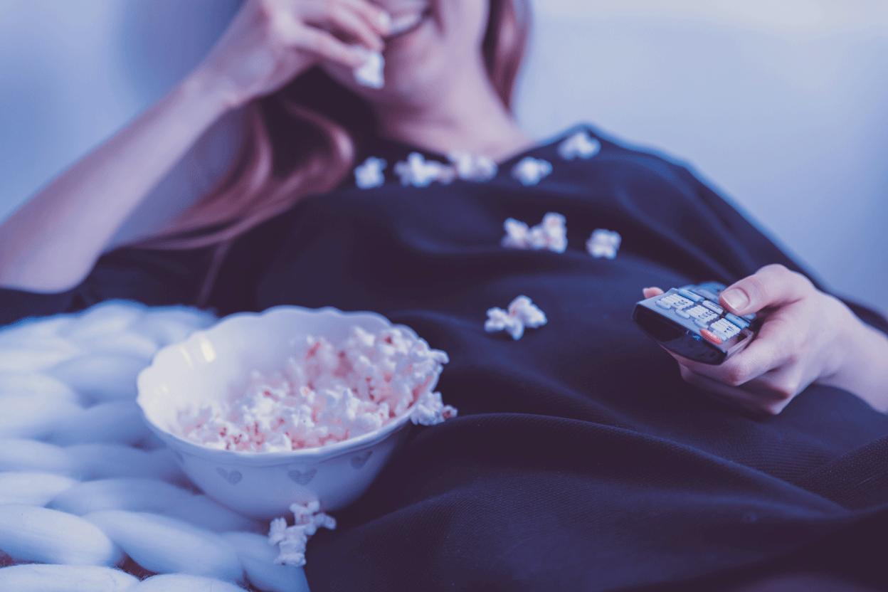woman in black dress eating popcorn movie light