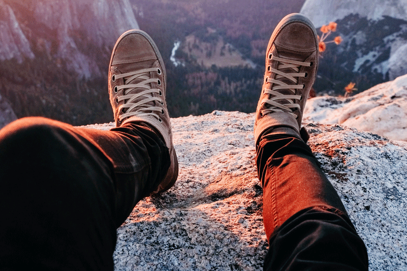 person laying near a cliff with converse on