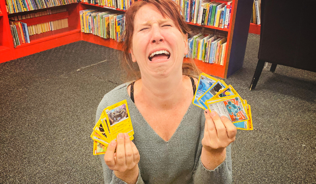 Woman holding Pokemon cards and crying in frustration