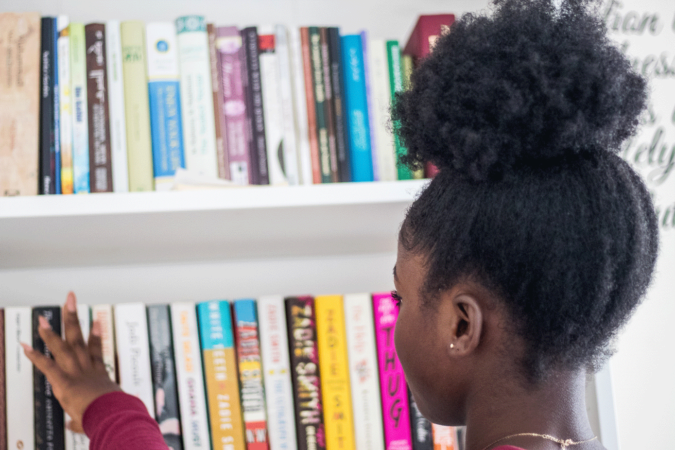 Black African-American little girl looking at books on bookshelf selecting a book
