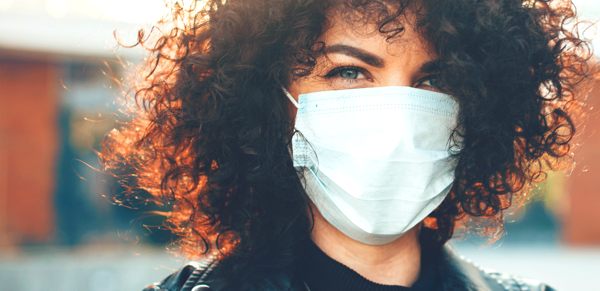 curly haired woman wearing a face mask in pubic